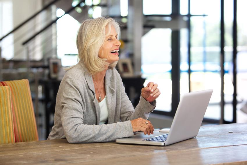 Glückliche ältere Geschäftsfrau am Laptop